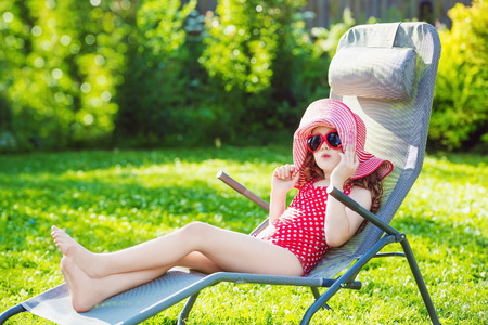 big hat: Funny little girl dressed in a red swimsuit, big hat and sunglasses heart sunbathes on a sun lounger.