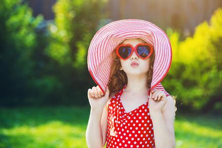 maillot de bain: Drôle petite fille habillée dans un coeur maillot de bain rouge, grand chapeau et des lunettes de soleil. L'enfant envoie un baiser d'air. Banque d'images