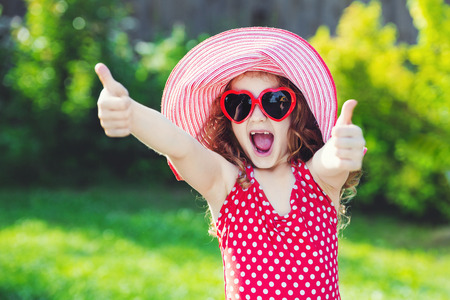 thumbsup: Laughing girl with red swimsuit, big hat and sunglasses heart shape, showing thumbs up.