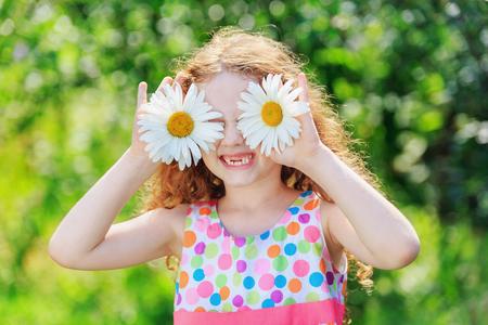 niños sonriendo: Niño con los ojos margarita con vestido de arco iris, sobre fondo verde bokeh en un parque de verano.