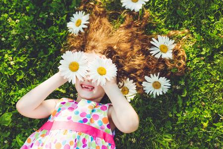 Dítě s sedmikrásky očí duha šaty, ležící na zelené trávě v létě parku. Reklamní fotografie
