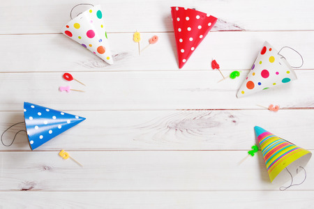 toning: Greeting card for carnival party. Party hat and candles on wooden background. Toning instagram filter. Stock Photo