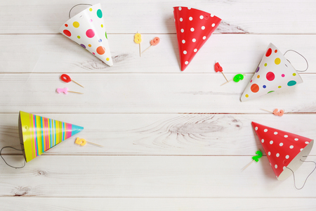child birthday: Greeting card for carnival party. Party hat and candles on wooden background.