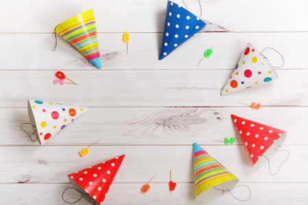 party background: Greeting card for carnival party. Party hat and candles on wooden background. Toning filter. Stock Photo
