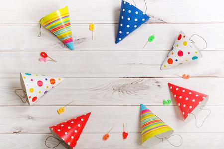 Tarjeta de felicitación para la fiesta de carnaval. sombrero de fiesta y velas en el fondo de madera. Tonificación filtro. Foto de archivo - 59673553