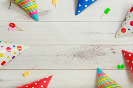 Greeting card for carnival party. Party hat and candles on wooden background.