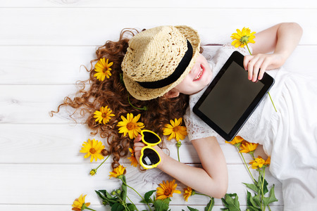 inulin: Laughing girl in a straw hat resting on the tablet in her hands. Dreaming of a rustic holiday.
