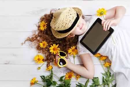 hearts background: Smiling girl in a straw hat resting on the tablet in her hands. Dreaming of a rustic holiday.