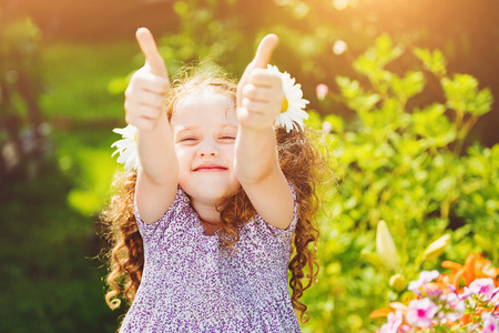 Laughing girl with daisy in her hairs, showing thumbs up. Stockfoto