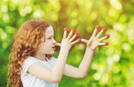 fruit eater: Little girl teasing is putting fingers to nose with raspberry.