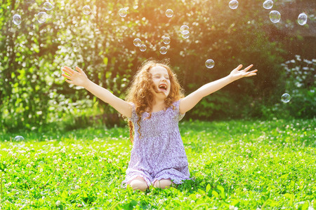 Laughing curly girl enjoy soap bubbles. Happy childhood concept. Imagens