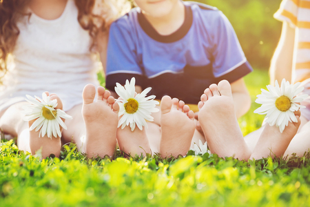 Children feet with daisy flower on green grass in a summer park. Stockfoto
