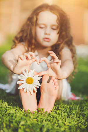 Child feet with daisy flower on green grass in a summer park. Hand show gesture with heart shape.