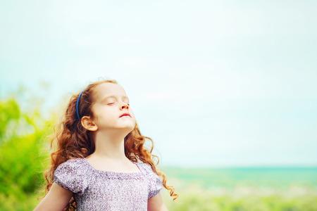 어린 소녀는 그녀의 눈을 감고 신선한 불어 오는 공기로 숨을 쉬었다. 건강 및 의료 개념입니다.