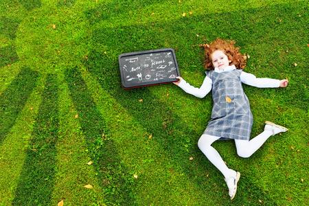 zapatos escolares: Chica pelirroja tendido en la hierba verde en el parque, vista superior alta, niñez feliz, de nuevo a escuela, concepto de la educación.