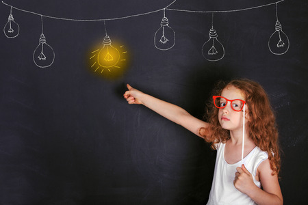 Smart child with red glasses points a finger at lighted lamp. Education and Leadership concept. Stock Photo