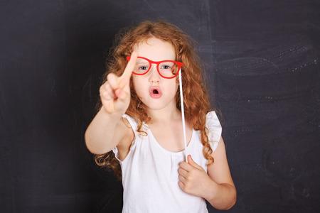 School girl montrant secouant le doigt en disant non, près de tableau noir.