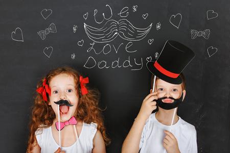 """niños riendose: Felices los niños dibujan """"Nos encanta papá"""" en la pizarra. Los gemelos lindos niños tienen bigote y la barba carnaval, el día de padre concepto. Foto de archivo"""