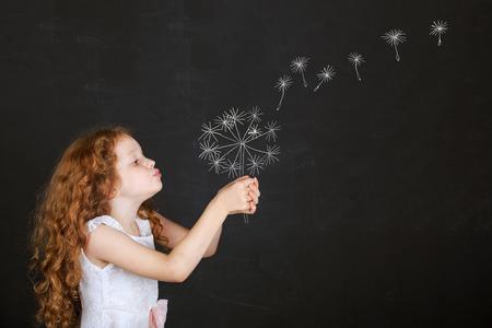 Little girl blowing dandelion with drawing in blackboard.