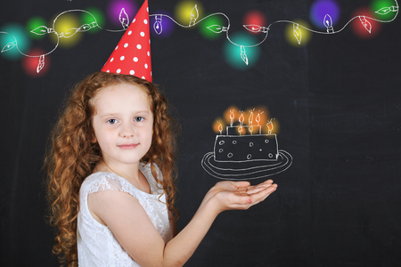 Little girl in birthday hat hold a birthday cake drawing on blackboard. Stock Photo