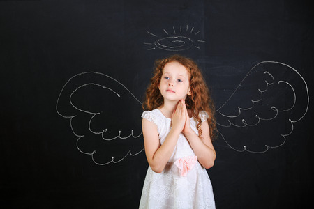 child praying: Cute girl in white dress folded her hand with praying, stand near angel wings drawn on a blackboard. Stock Photo