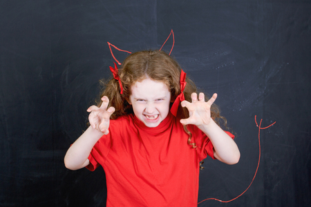 Angry girl in red t-shirt stand near horns and devil tail handdrawing on blackboard. Child character. Health and medical concept. Stock Photo
