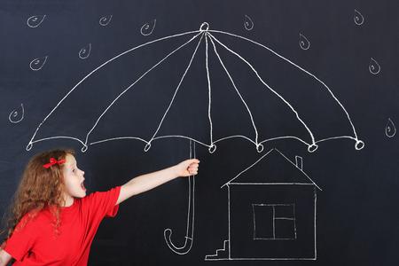 Niño en camiseta roja toma de refugio de las miserias y la lluvia bajo un paraguas. Concepto de protección de su casa. Foto de archivo