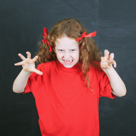Child in red t-shirt with aggression  in pose.