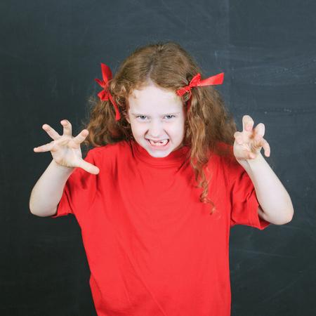 conflictos sociales: Ni�o en camiseta roja con la agresi�n en pose. Foto de archivo