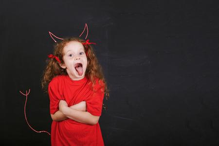 Nettes Mädchen im roten T-Shirt stand in der Nähe mit imp Hörnern und Schwanz auf eine Tafel gezeichnet. Kinder Charakter.
