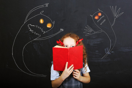 Child hiding behind the book, and is afraid near chalkboard. Education concept. Archivio Fotografico