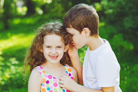 Surprised little girl and boy talking with whispers. Toning to instagram filter. Stock Photo