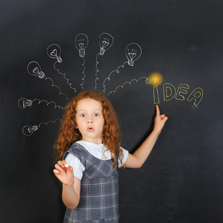 lighted: Smart child with red glasses points a finger at lighted lamp. Education and Idea concept.