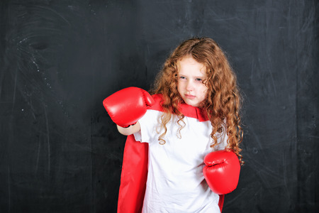 freedom fighter: Little girl in red boxing gloves showing aggressive face expression stand near chalkboard. Education, success, feminism, winner, leadership concept.