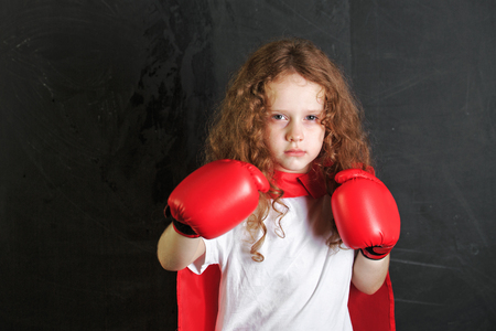 people in action: Child in red boxing gloves stand near chalkboard. Stock Photo
