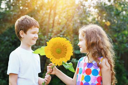 gemelos niÑo y niÑa: funy niños que sostienen el girasol en un día soleado. Cuidado de la salud, concepto de infancia médica y feliz.