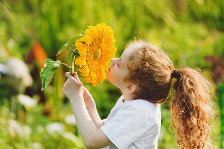 여름 화창한 날 자연을 즐기는 즐거운 아이 냄새 해바라기. 건강, 자유와 행복 어린 시절 개념.