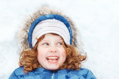 Little girl lying on a snow. Child enjoying nature on a winter walk in sunny day.