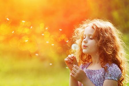 Bello bambino godere soffia dente di leone nel parco di primavera. Bambina riccio con fiore di primavera nella luce del tramonto. Archivio Fotografico