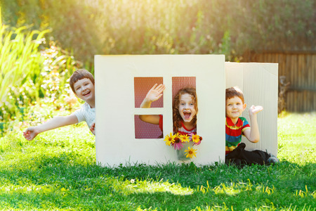 Laughing children play in the house made of cardboard box. Little boy and girl dream about new home and family.