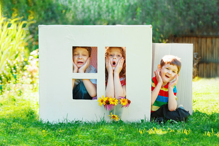 Sad children play in the house made of cardboard box. Little boy and girl dream about new home and family.