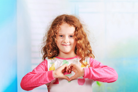 showing: Little girl showing heart with hands. Peace, love, happy childhood, healthy lifestyle concept.