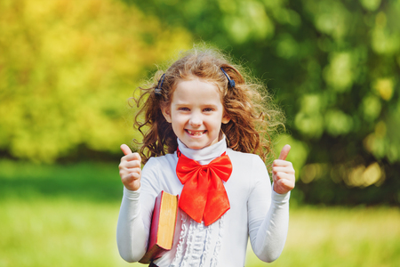 Schoolgirl in school uniform  showing thumbs up in the park. Back to school, happy childhood, successful concept. Stock Photo