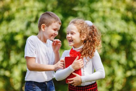 niño escuela: Los pequeños susurros de ninos en el parque.