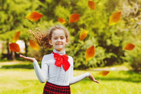 Happy schoolgirl in school uniform  jump and throws the autumn leaves in the air. Back to school, happy childhood  concept.