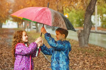 Children under umbrella enjoy to autumn rain outdoors.