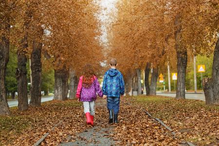 manos entrelazadas: niño y niña de la mano caminando en la carretera otoño. Vista de la parte trasera.