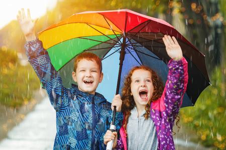 sotto la pioggia: Bambini sotto l'ombrello giornata di pioggia autunnale all'aperto. Archivio Fotografico
