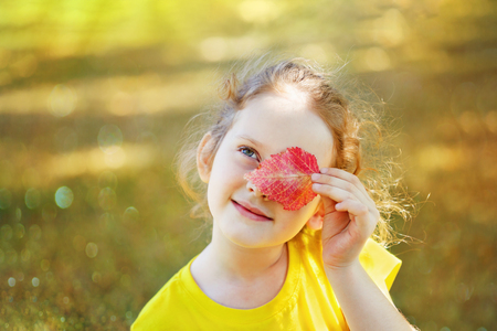 sun glasses: Beautiful Little girl holding leaf near eyes and funny smile in golden autumn park.