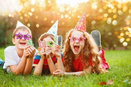 Happy child friend in carnival party, lying on a green grass in sunset light. Creative invitation for party, holiday, wedding, birthday, christmas, New Year concept.